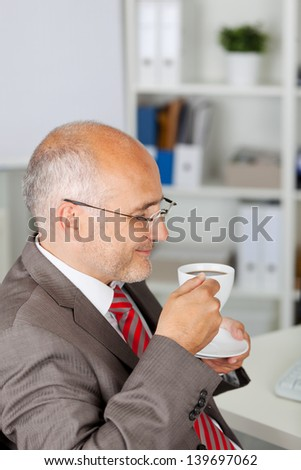 businessman enjoying a cup of coffee with closed eyes - stock photo