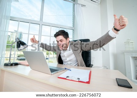 Businessman enjoys from working at a laptop. Young successful businessman throws up his hands to the side and looking at the laptop while sitting at a desk and a laptop in the office - stock photo