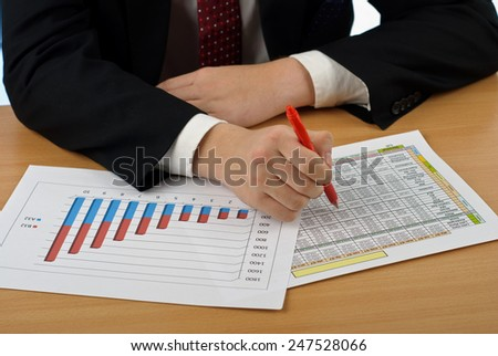 Businessman examining graphs at desk in his office - stock photo