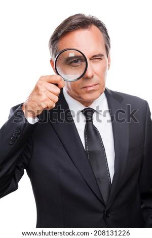 Businessman examining you. Serious mature man in formalwear examining you with magnifying glass while standing isolated on white background