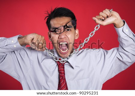 Businessman excpressing his anger with chain around his neck - stock photo