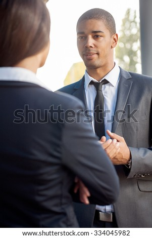 Businessman explaining colleague about work, outdoors - stock photo