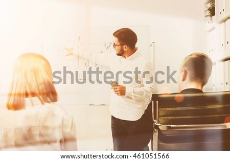 Businessman explaining drawing on whiteboard to his sitting colleagues while holding cell phone in his hand. Concept of teamwork and brainstorming. Toned image.