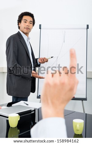 Businessman explaining graph on filpchart with colleague raising hand in conference room - stock photo