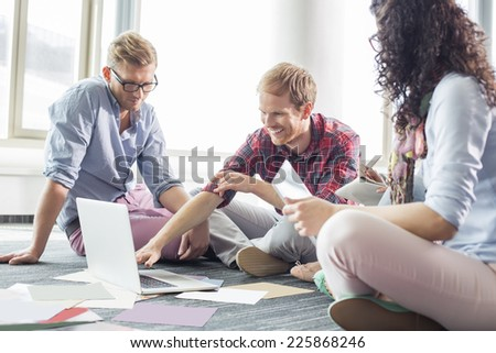 Businessman explaining plan on laptop to colleagues at creative office - stock photo