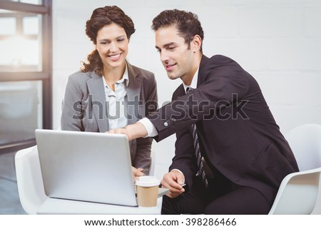 Businessman explaining smiling female colleague over laptop in office