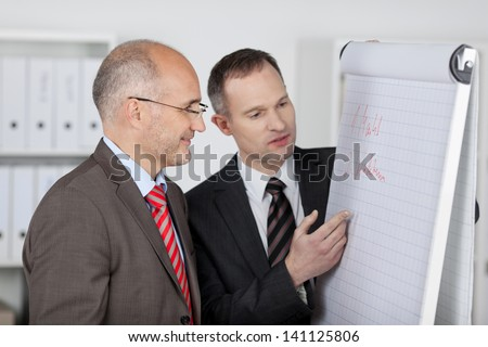 Businessman explaining with flipchart to his partner inside the office - stock photo