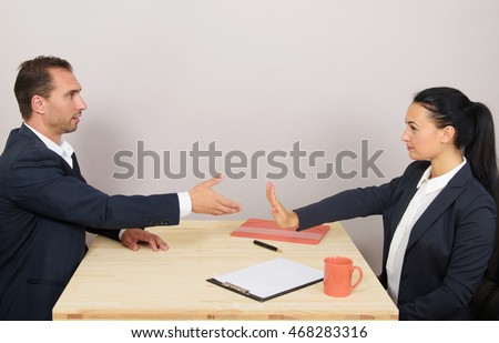 Businessman extending arm for handshake, businesswoman stopping him