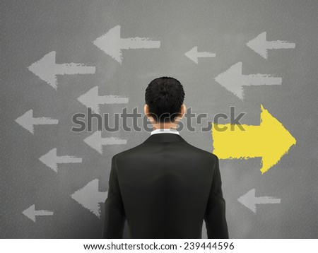 businessman faces left or right choices over grey - stock photo