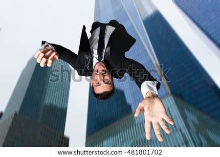 Businessman falling down from a tall skyscraper