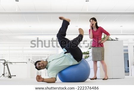 Businessman Falling Off Exercise Ball - stock photo