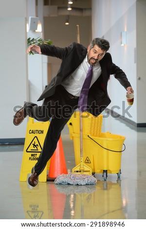 Businessman falling on wet floor inside office building - stock photo