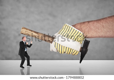 Businessman fighting with a hand with blank work glove - stock photo