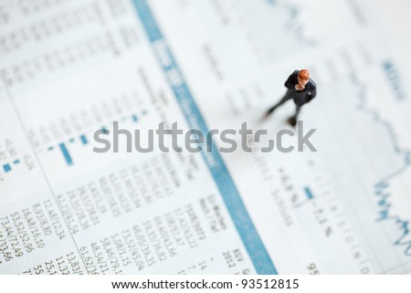 businessman figurine on a magazine with equity prices - stock photo