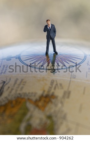 Businessman Figurine on Globe - stock photo
