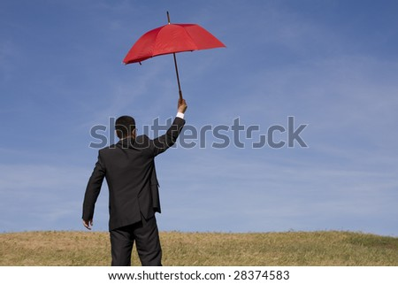 Businessman finding protection outside in the field - stock photo