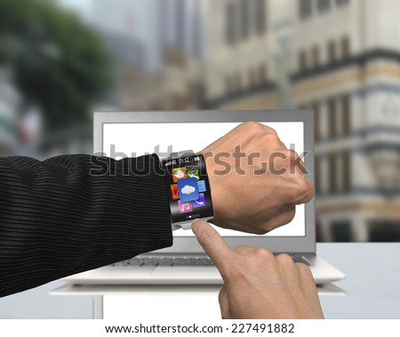 businessman finger point app icons of smartwatch with bent interface and metal watchband on laptop street background - stock photo