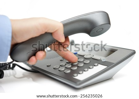 Businessman finger pressing a number button on the land line telephone - stock photo