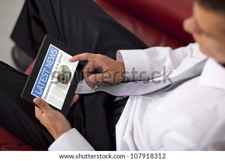 Businessman finger touching screen of a digital tablet and sitting on couch - stock photo