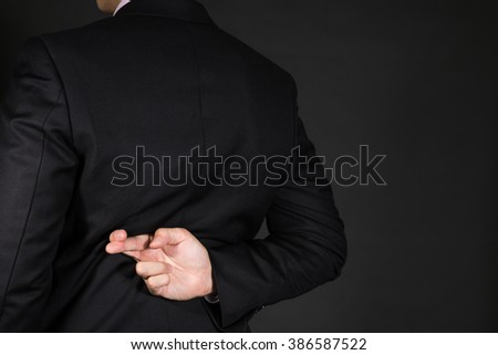 Businessman fingers crossed behind his back - stock photo