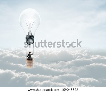 businessman flying in air baloon with lamp - stock photo