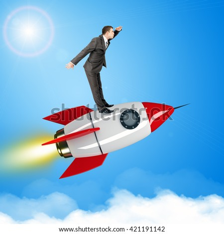 Businessman flying on jet rocket above city in sky - stock photo