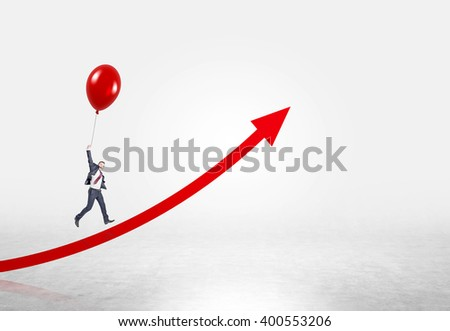 Businessman flying up on red balloon over red arrow. Concrete background. Concept of career growth.