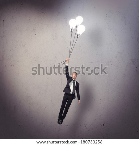 Businessman flying with light bulbs - stock photo