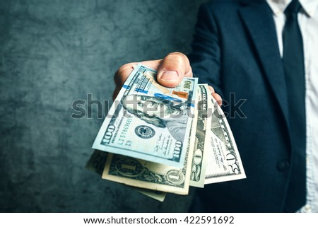 Businessman from bank offering money loan in USA dollar banknotes, selective focus. - stock photo