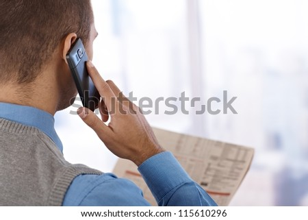 Businessman from behind with mobile phone, holding newspaper, at skyscraper window. - stock photo