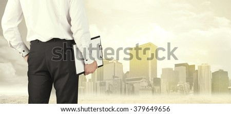 Businessman from the back in front of a city view with sunshine - stock photo