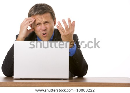 Businessman Frowning While Looking At Laptop - stock photo
