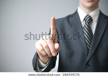 Businessman gesture with his hands on gray background - stock photo
