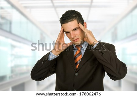 Businessman gestures with a headache, at the office