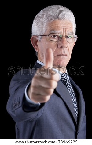 Businessman gesturing OK with his thumb (isolated on black) - stock photo