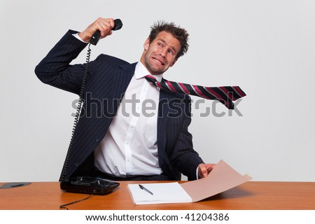 Businessman getting a phone call from an angry person shouting down the line. - stock photo