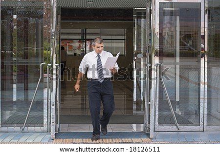 Businessman getting out of a corporate building while reading something in a notebook.