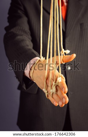 Businessman gives a handshake, hand on the ropes, concept of managing people - stock photo