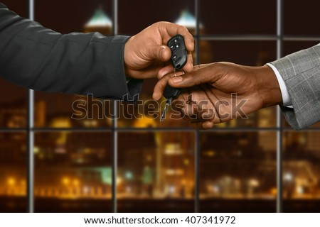 Businessman gives car key away. Men passing key at night. Ready for a test-drive. Sign of trust.