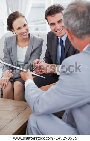 Businessman giving a contract to his partners in cosy meeting room