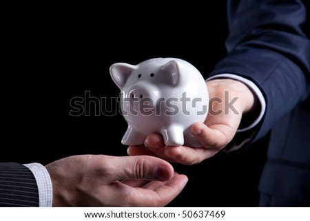 Businessman giving a piggy bank to you (isolated on black) - stock photo