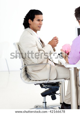 Businessman giving a piggybank to his colleague at work - stock photo