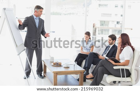 Businessman giving a presentation to co-workers - stock photo