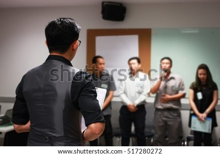 Businessman giving an explanation as he stands doing a presentation to his business team or group of co-workers, view from behind their backs