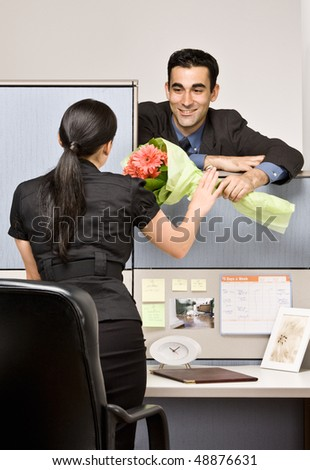 Businessman giving co-worker flowers - stock photo