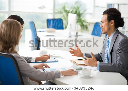 Businessman giving financial report in front of entrepreneurs - stock photo