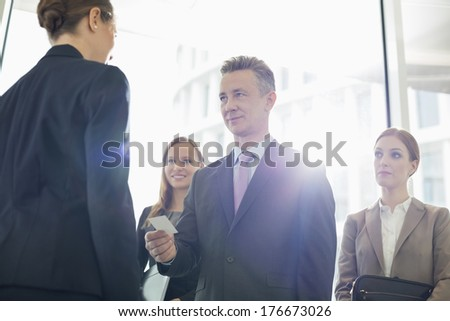 Businessman giving his card to female coworker in office - stock photo