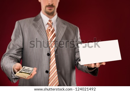 Businessman giving money, blank card in other hand - stock photo