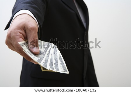 Businessman giving money isolated on white