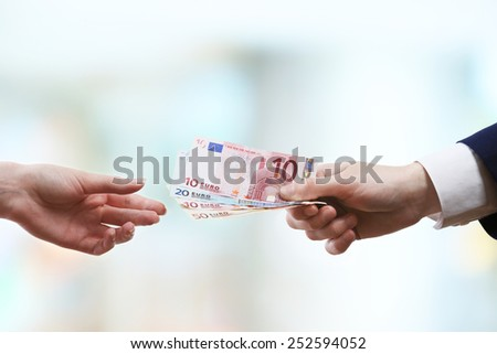Businessman giving money on light blurred background - stock photo